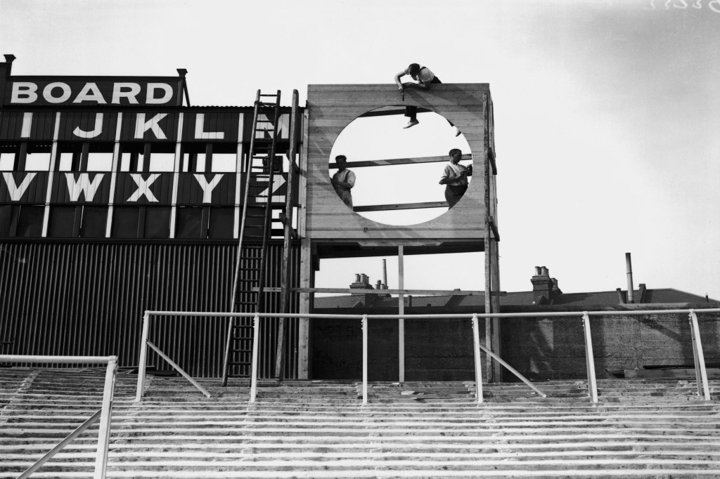 28th August 1930: Workmen attending to the score-board at Arsenal Football Club grounds. (Photo by Fox Photos/Getty Images)